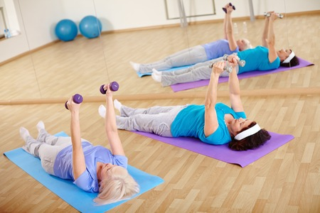 Mature women doing exercise with barbells in gym photo