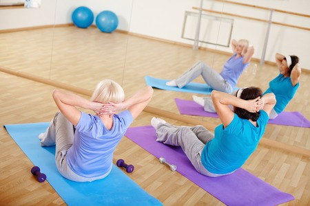 Mature females doing sit-ups on mats in sport gym  photo