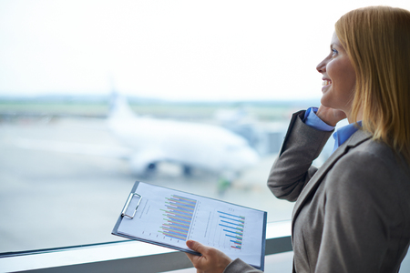 Charming manager with document speaking on cellular phone in airport photo