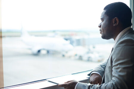 Serious businessman with digital tablet looking through window in airport photo