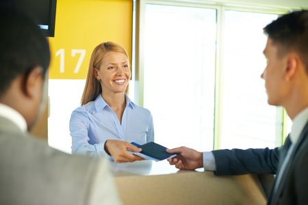flight: Smiling female returning passport and tickets to businessman in airport Stock Photo