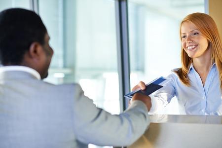 gente aeropuerto: Mujer joven atractiva que da el pasaporte y el billete de vuelta a empresario en el aeropuerto mostrador de facturaci�n Foto de archivo