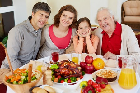 Portrait of happy family sitting at festive table on Thanksgiving day photo
