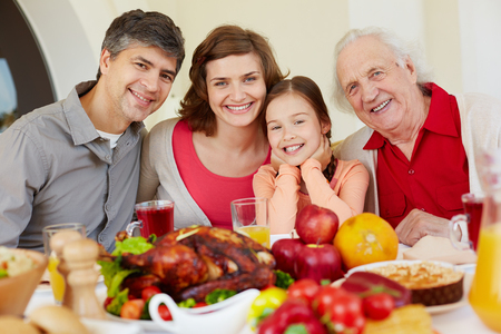 Happy family of four sitting at festive table on Thanksgiving day photo