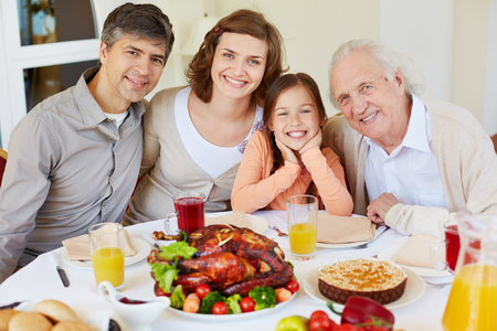 Portrait of happy family members sitting at festive table on Thanksgiving day and looking at camera photo