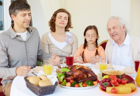 Portrait of family of four praying at festive table on Thanksgiving day photo