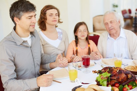 Family of four praying at festive table on Thanksgiving day, focus on young man photo
