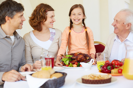 thanksgiving adult: Portrait of happy family looking at joyful girl during Thanksgiving dinner
