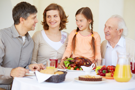 Big family looking at young man during traditional Thanksgiving dinner photo