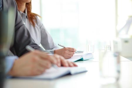 Hand van zakenvrouw met balpen over open notebook op conventie