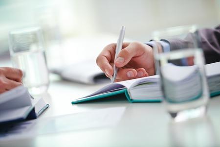 sessão: Mãos masculinas e femininas que fazem anotações ou escrever plano de trabalho Imagens