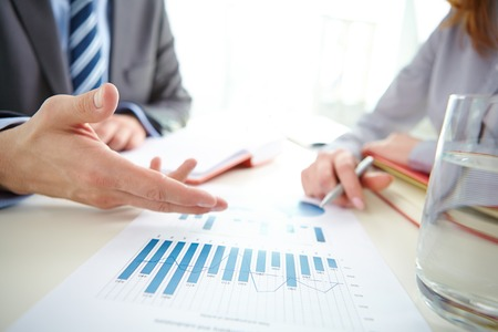 Businessman hand pointing at chart and graph during discussion photo