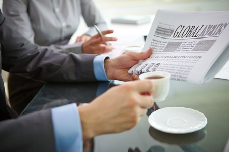 Businessman with newspaper having coffee at workplace photo