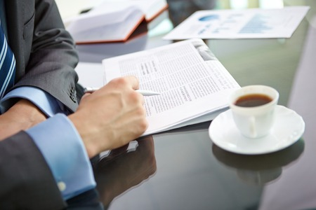 Male hand with pen over newspaper and cup of coffee near by photo