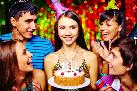 Attractive girl with birthday cake and her friends having party photo