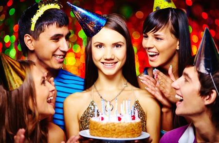 Attractive girl holding cake and looking at camera with her friends congratulating her near by photo