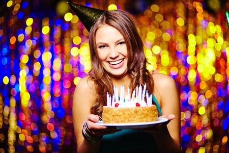 Laughing woman with birthday cake looking at camera photo