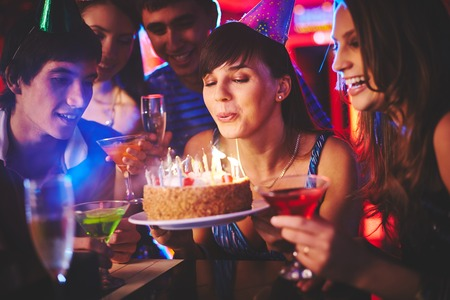 Happy girl blowing on candles on birthday cake with her friends near by photo