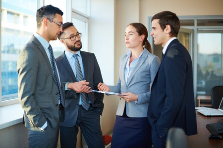 Group of colleagues discussing documents and business plans in office photo