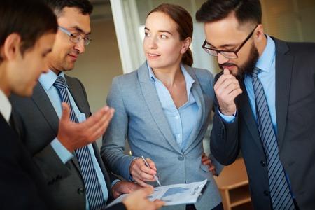 reuniones empresariales: Sonriendo empresaria que se�ala el documento mientras que explic�rselo a sus colegas