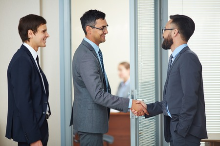 Two businessmen handshaking in office after signing contract photo