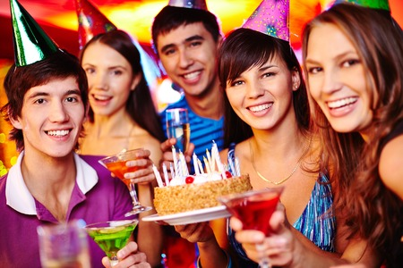 Portrait of joyful friends with birthday cake and drinks looking at camera at party photo