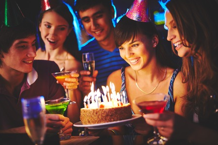 Charmed girl looking at birthday cake with burning candles at party, her friends surrounding her