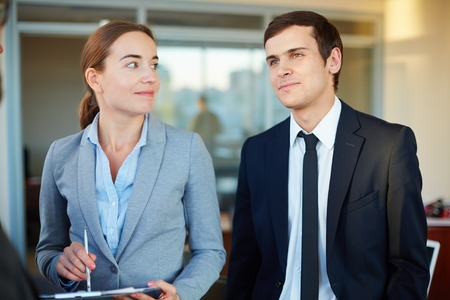 Pretty businesswoman looking at her male colleague in office