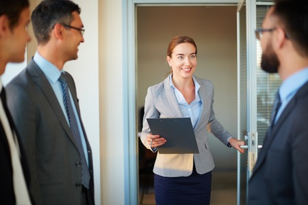 Happy businesswoman with clipboard entering office Stock Photo