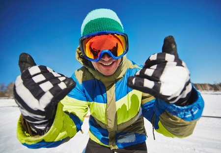 Young snowboarder in sportswear looking through protective eyeglasses at winter resort Stock Photo - 31704548