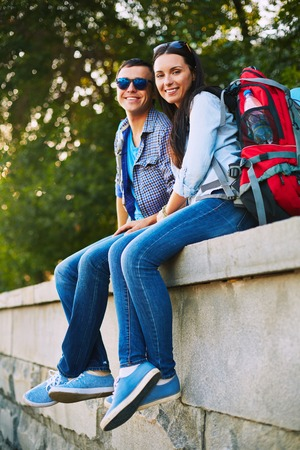 restful: Restful travelers with rucksacks sitting in park and looking at camera