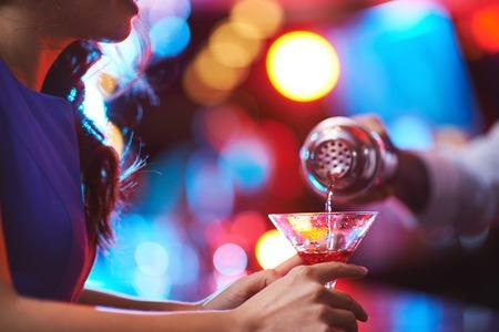 tomando alcohol: Chica joven que sostiene el vidrio de martini con la bebida roja en la barra