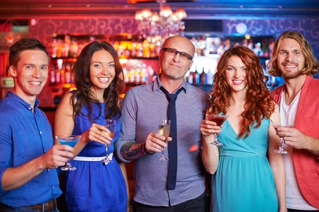 friends drinking: Group of boozing people with drinks looking at camera at party