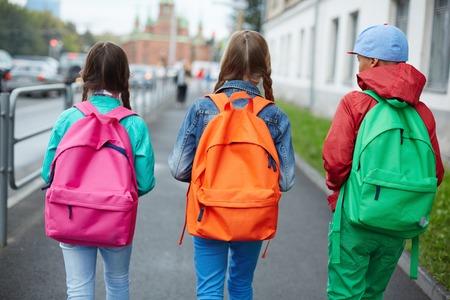 niños saliendo de la escuela: Realiza copias de seguridad de colegiales con mochilas de colores que se mueven en la calle