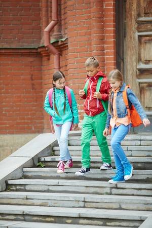 niños saliendo de la escuela: Amigos de la escuela lindos en ocasional bajando escaleras Foto de archivo
