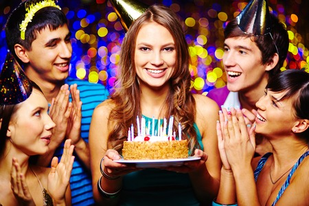 Beautiful young female with birthday cake looking at camera, her friends applauding photo