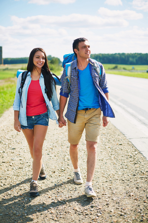 Couple of young hitch-hikers walking along highway photo