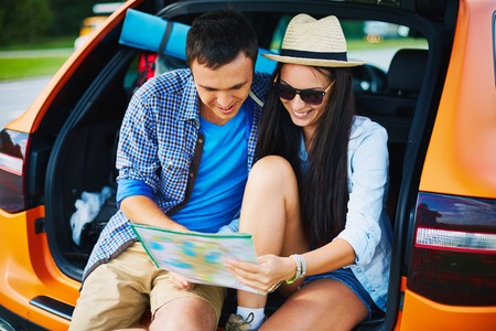 car trunk: Young travelers looking at map while sitting in trunk of a car Stock Photo