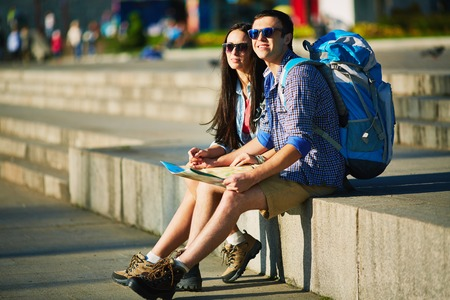 restful: Restful travelers with map deciding where to go while sitting on edge of stairs Stock Photo