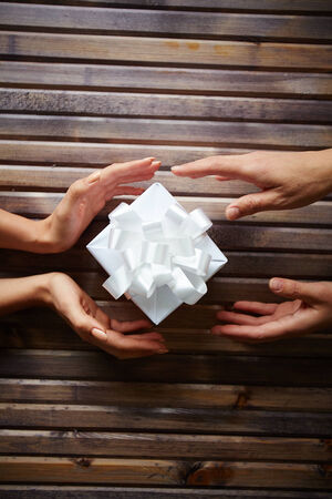 traditional gifts: Hands of woman giving Christmas present to her friend