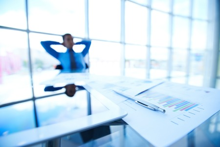 Business documents, touchpad and pen at workplace on background of male employee photo