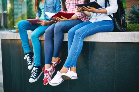 jeans: Casual teen girls in jeans reading outside