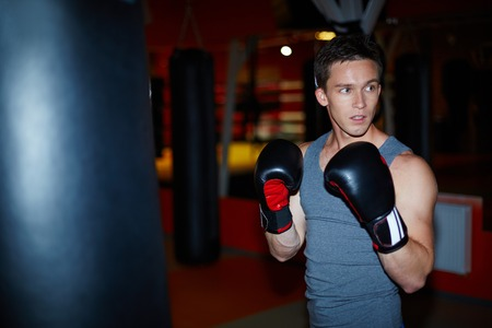 boy boxing: Portrait of young man in boxing gloves in sports gym