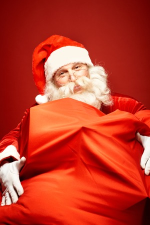 huge: Portrait of happy Santa Claus with gigantic sack full of gifts looking at camera Stock Photo