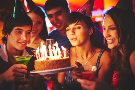 velitas de cumpleaños: Encanto femenino que sopla en velas en la torta de cumpleaños después de hacer su voluntad en la fiesta