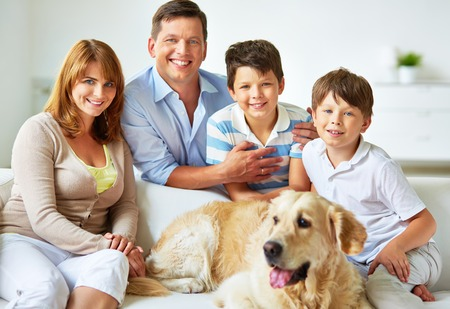 Parents and children with their pet having rest photo
