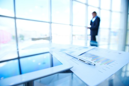 business report: Business documents, touchpad and pen at workplace on background of businessman calling by the window Stock Photo