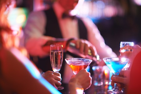 company party: Hands of young people holding martini and champagne in the bar