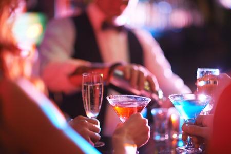 copa martini: Manos de jóvenes con martini y champán en el bar