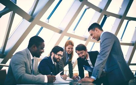 colaboracion: Grupo de personas de negocios feliz en discusiones sobre documentos en la reuni�n Foto de archivo